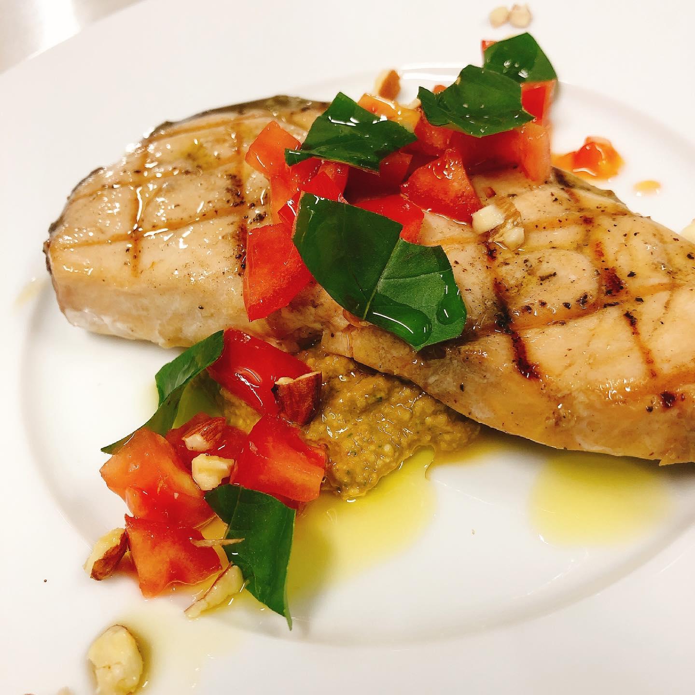 和歌山産カジキマグロのグリル シチリア風アーモンドのソース  今回入荷の生のカジキマグロ(マカジキ)は中々入らないお魚で、多少スジはありますが、身の旨みがしっかりとある美味しいお魚です。  同じくカジキマグロと言われているお魚でもスーパーでよく見るメカジキとは別物です。 メカジキは脂身が多く白い身で、マカジキは赤みがかった身で旨みが濃いのか特徴です。  そのカジキマグロをシンプルにグリルし、シチリア州トラパニ風のアーモンドとトマトとバジリコのペースト(ペスト・トラパネーゼ)をソースにしました。  とっても美味しく出来ましたのでぜひお試しください 本日もよろしくお願い致します🏻  #マカジキ  #カウンター席 あります 美味しいグラスワインあります #肉の盛り合わせ  手打ちパスタ ピッツァ #イタリア料理  パラヴィーノワインアカウント @paravino.vino パラヴィーノテイクアウトアカウント @paravino.takeout